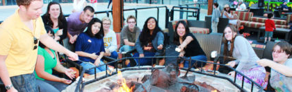 New to SNU Tahoe, students mingle around a fire at Northstar for 日eir 新的学生取向
