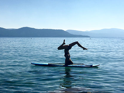 journalism student kyly clark does a headstand on her paddleboard on Lake Tahoe