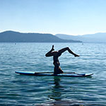 Kyly Clark, interdisciplinary studies major in journalism and digital arts and yoga devotee, doing a headstand on a paddleboard on Lake Tahoe.