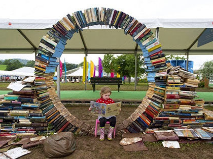 Child encircled with books at book fair in Hay-on-Wye, Wales famous as the Town of Books