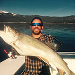 Andrew Lubrano, Finance and Economics major, poses with big catch on his boat on Lake Tahoe