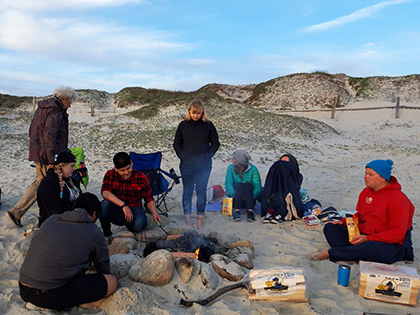 学生们 building a bonfire on the beach in Monterey during a Sierra Nevada College science trip.