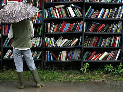 "Women browsing books in the rain in Hay-on-Wye, Wales famous as the ""Town of Books"""