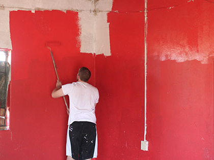 Student in 纬来体育网址 South Africa Service Learning Africa course renovating a rural preschool - painting the walls red!