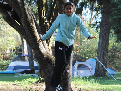 student enjoying the slack line at the campsite in Coloma CA at the Sierra Nevada University orientation river camp adventure