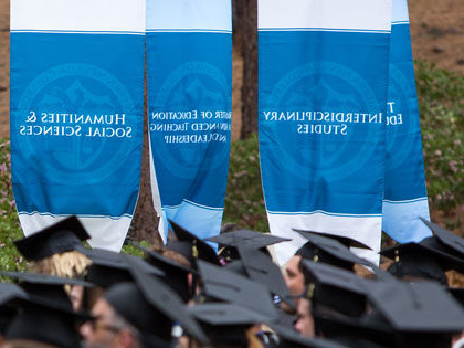 graduates in their mortar boards can be seen below academic banners at the 2019 Sierra Nevada College Commencement