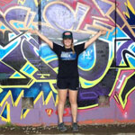 Madeleine Hall, Marketing major, poses in front of brightly painted wall