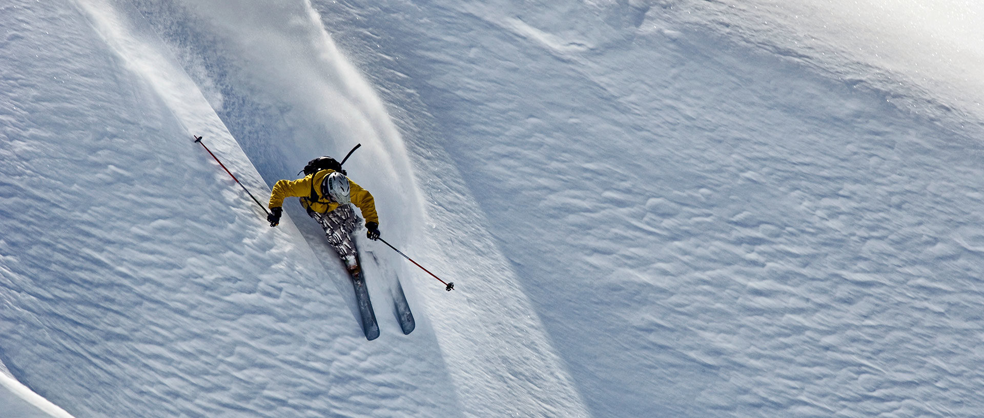 a skier in a yellow jacket makes the first run in fresh powder