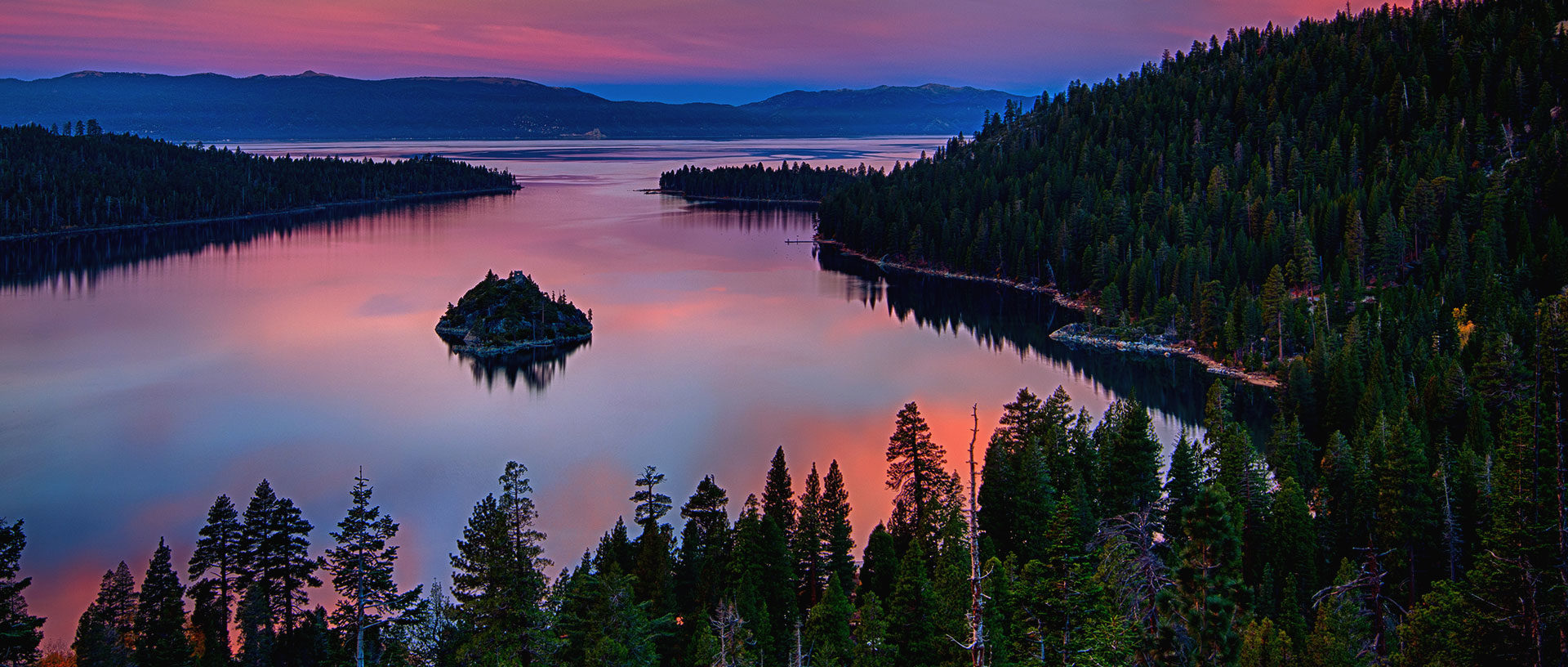A colorful sunset reflected in the water of Emerald Bay on the Lake Tahoe shore